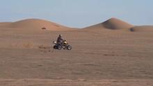 A Man Racing Past Sand Dunes On An ATV