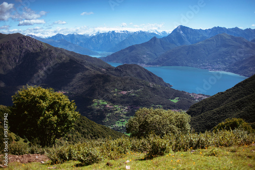 Keuken foto achterwand Zwart Panoramic View of beautiful landscape in the Italian Alps with fresh green meadows and snow-capped mountain tops in the background on a sunny day with blue sky and clouds in springtime.