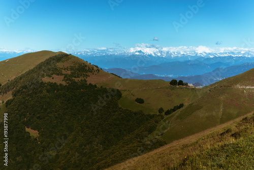 Poster Blauw Panoramic View of beautiful landscape in the Italian Alps with fresh green meadows and snow-capped mountain tops in the background on a sunny day with blue sky and clouds in springtime.