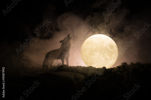 Silhouette of howling wolf against dark toned foggy background and full moon or Wolf in silhouette howling to the full moon Wallpaper Mural