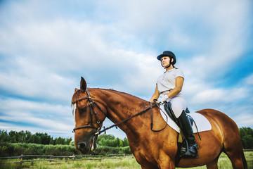Fototapeta Girl jockey riding a horse