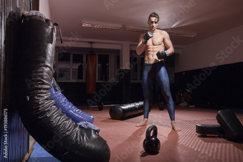 Fotomural one boxer posing, indoors, boxing bag, fitness boxing equipment, flooring