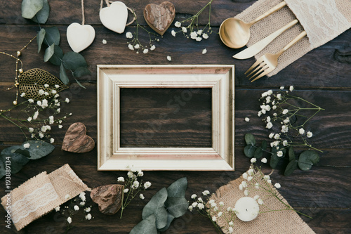 Fotografía  Details of a rustic wedding with gold frame over wooden background