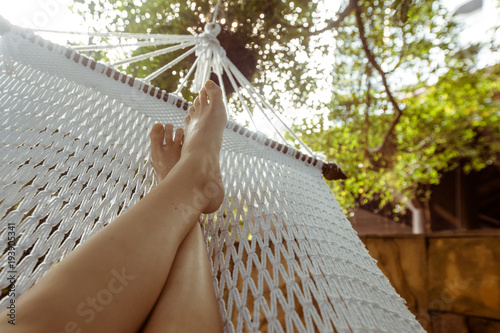 Crop shot of barefoot feet lying in white hammock and lounging in backyard.