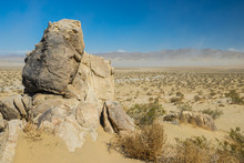 Tall Stone Boulder Stands Above Massive Sand Wilderness In The Desert Of Southern California.
