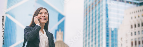 Fototapeta Asian businesswoman talking on mobile phone in Hong Kong cityscape background panoramic banner. Young chinese woman calling on smartphone happy. Multiracial Chinese Caucasian lawyer. obraz