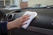 woman wipes dust in the car