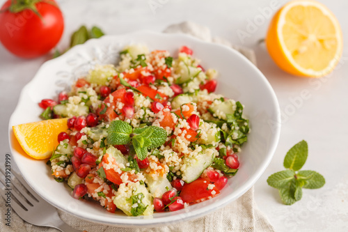 Tabbouleh salad with tomato, cucumber, couscous, mint and pomegranate. Vegan Healthy Food Concept. Traditional middle eastern or arab dish.