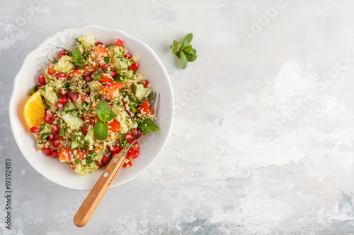 Tabbouleh salad with tomato, cucumber, couscous, mint and pomegranate. Top view, copy space, gray background. Vegan Healthy Food Concept. Traditional middle eastern or arab dish.