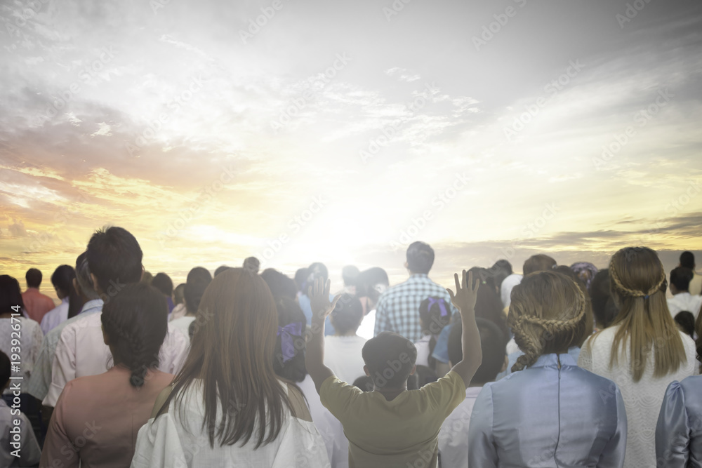 Fototapeta soft focus of christian people group raise hands up worship God Jesus Christ together in church revival meeting with image of wooden cross over cloudy sky can be used for Christian worship background