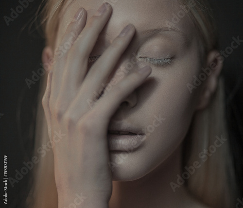 Photo Young albino woman with closed eyes touches her face.