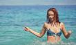 Pretty beautiful woman in white swimwear bikini posing in blue sea water