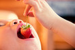 Close up Strawberry fruit on Boy hand are put mouth to eat.