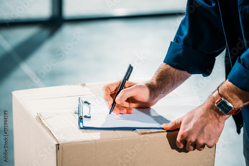 Fotomural Courier filling cargo declaration on cardboard package