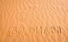 Abu Dhabi Handwritten Text In Desert Sand.