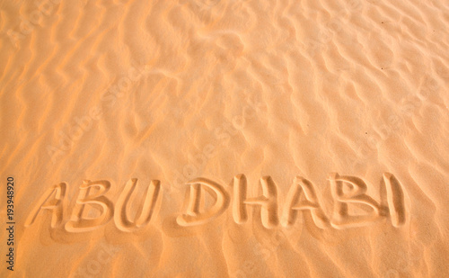 Abu Dhabi handwritten text in desert sand.