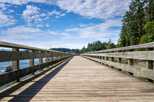 Empty Wooden Pier Under Blue Sky With Clouds On A Summer Morning. Sooke, BC, Canada.