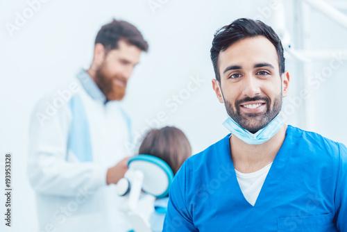 Fotomural  Portrait of a confident dental surgeon wearing blue protective uniform and surgi