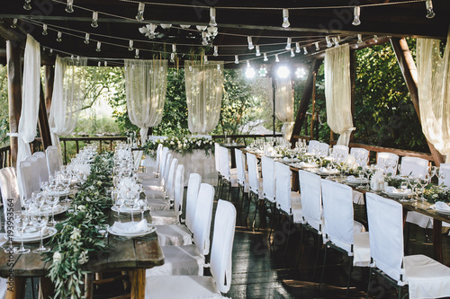 Fototapeta Decorated elegant wooden wedding table for banquet outdoor in garden gazebo with lamp, in the style of rustic with eucalyptus and flowers, porcelain plates, glasses, white chairs obraz