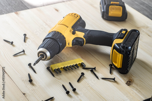 Photo yellow screwdriver on a wooden table, screws, a set of bits.