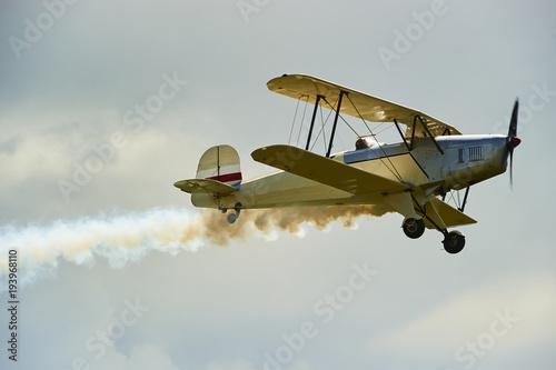 Vintage single engine propeller biplane aircraft flying against sky Canvas Print