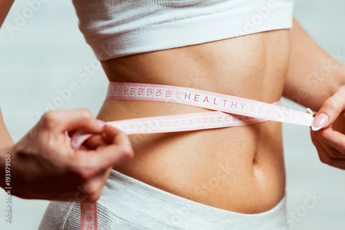 Beautiful, fit, young woman measuring her waist with a measuring tape, with word Fototapeta