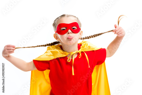 Платно Little supergirl in yellow cape and red mask for eyes showing tongue and holding
