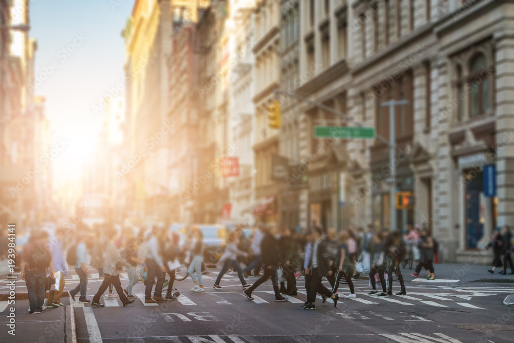 Anonymous crowd of people walking across the intersection in SoHo New York City