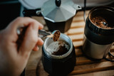 Preparing fresh coffee in moka pot on electric stove. Measuring ground coffee for moka pot. Hand holding measuring spoon.