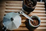 Preparing fresh coffee in moka pot on electric stove. Measuring ground coffee for moka pot.