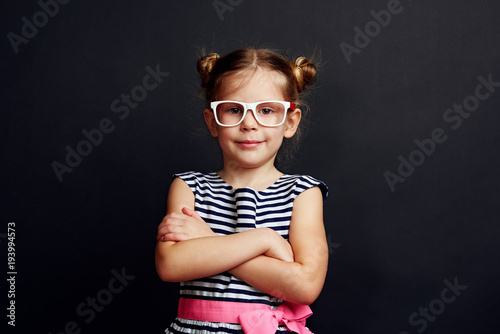36ae0cde2f3 Fashion portrait of adorable girl in specs with stylish hairdo over studio  background.