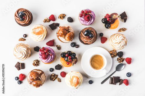 Photo  flat lay with arrangement of sweet cupcakes, teaspoon and cup of coffee isolated