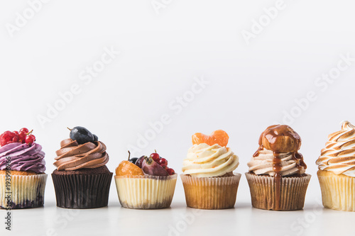 Photo  close up view of various sweet cupcakes isolated on white