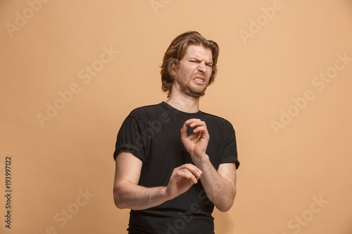 Young man with disgusted expression repulsing something, isolated on the pastel Slika na platnu
