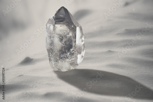 Large quartz crystal on a snowy background close-up