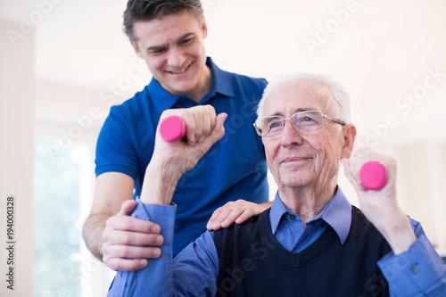 Obraz Physiotherapist Helping Denopr Man To Lift Hand Weights - fototapety do salonu