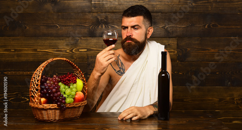 Fotografía  God of wine with serious face sits by wine bottle