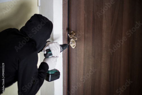 Crime, robbery, masked thief, burglar, trying to break into a flat, a drill in t Canvas Print