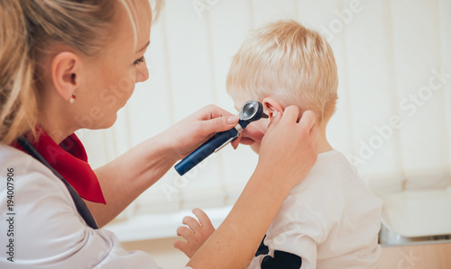 Doctor examines ear with otoscope in a pediatrician room. Canvas Print