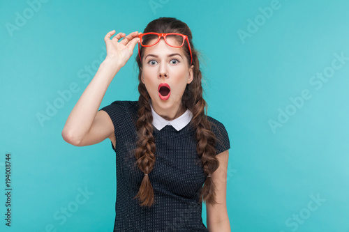Photo Surprised woman in red glasses amazement looking at camera