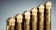 Münzstapel mit goldenen Modellhäusern