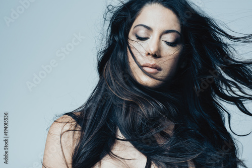 Beautiful young woman with long black hair against blue background Poster