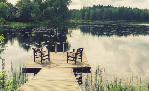 Valokuva  Two wooden chairs on the pier by the pond