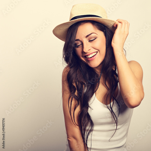 Fotografie, Obraz  Beautiful long hair laughing woman in white top and straw hat looking happy