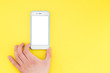 canvas print picture The human hand with a smartphone is isolated on a yellow background. The hand holds the phone down. Template for design.