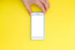canvas print picture Flat lay hand with phone. The hand holds a smartphone with a white screen on top of a yellow background. Hand with phone isolated on yellow background.