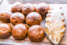 Closeup Of Fresh Brown Scored Sourdough Baked Bread Loaves In Bakery With Many Buns Rolls