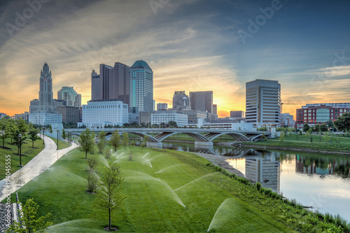 Obraz Skyline along the Scioto River showcasing the Leveque Tower and Supreme Court building with sprinklers activated.  - fototapety do salonu