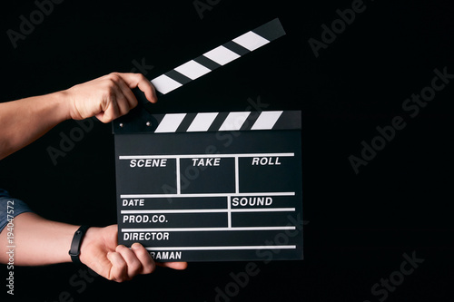 Canvas Print Hands with a movie clapperboard isolated on black background with copy space, close-up