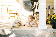 Girl Lying By Dog On Porch